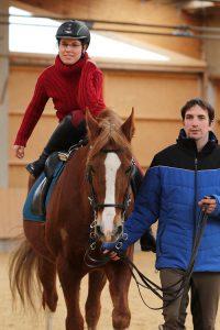 Sonja Kutter, Trainerin auf dem Josenhof im bayerischen Rot an der Rot, demonstriert den Hopserlauf auf dem Pferd.